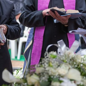 Three,Anglican,Priests,Attending,A,Funeral,,Next,To,The,Grave